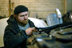 O homem do mecânico repara o corpo de carro fotos de stock royalty free