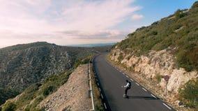 O homem do moderno monta no skate na estrada da montanha vídeos de arquivo