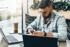 O homem do moderno senta-se no café, usa o smartphone, trabalha em dois portáteis O homem de negócios lê uma mensagem de informaç imagens de stock royalty free