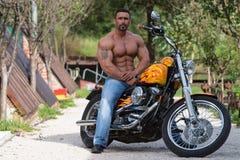 O homem do motociclista senta-se em uma bicicleta fotos de stock royalty free