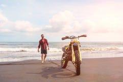 O homem do motociclista vai a seu velomotor do esporte na praia do oceano Fotografia de Stock