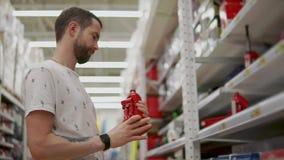 O homem do motorista está mantendo um jaque de elevador pneumático disponivel em uma loja para automobilists filme
