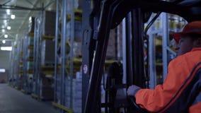 O homem do motorista inspeciona a fábrica no caminhão de empilhadeira que conduz através das cremalheiras com mercadoria filme