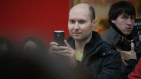O homem do movimento lento no preto entre povos e toma a foto video estoque