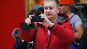 O homem do movimento lento no revestimento vermelho toma a foto em Smartphone video estoque