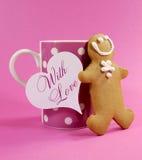 O homem do pão do gengibre do Feliz Natal com a xícara de café cor-de-rosa do às bolinhas e a amostra text Imagem de Stock Royalty Free