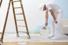 O homem do pintor no trabalho toma a cor com a escova de pintura dos bu Imagens de Stock