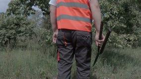 O homem do pomar com jardineiro scissors perto da árvore de maçã video estoque