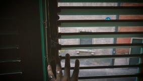 O homem do POV abre os obturadores da janela velha que olham à rua da cidade italiana velha video estoque