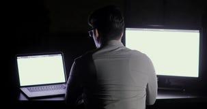 O homem do programador está trabalhando no escritório fora do tempo estipulado tarde na noite que senta-se antes de dois monitore video estoque