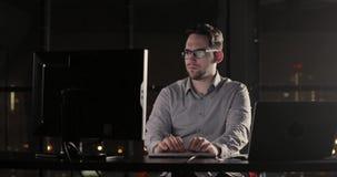 O homem do programador está trabalhando no escritório que datilografa fora do tempo estipulado no teclado tarde na noite vídeos de arquivo