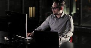 O homem do programador está trabalhando no escritório tarde em horas extras da noite vídeos de arquivo