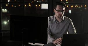 O homem do programador do hacker está trabalhando no escritório tarde em horas extras da noite filme