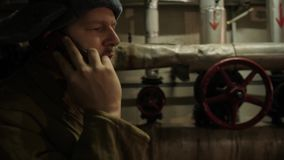 O homem do russo em um chap?u com os earflaps, falando no telefone em um por?o escuro e decide mat?rias da import?ncia nacional vídeos de arquivo