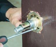 O homem do ` s da mão com chave de fenda instala o botão de porta foto de stock royalty free