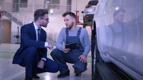 O homem do técnico com tabuleta comunica-se com o consumidor perto da roda de carro na loja de reparação de automóveis vídeos de arquivo