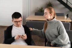 O homem do tapeador que data na linha com um telefone e uma amiga espertos está espiando o assento em um sofá no café foto de stock