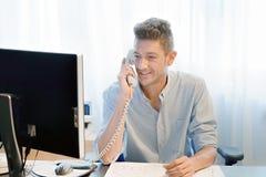 O homem do trabalhador de escritório responde à chamada fotografia de stock