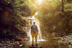 O homem do turista alcançou o destino e aprecia a vista da cachoeira, vista traseira, conceito da aventura do projeto imagens de stock