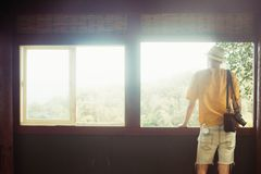 O homem do turista com uma câmera em férias para apreciar negligencia a opinião ensolarada da floresta do balcão da janela imagem de stock royalty free