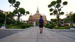 O homem do turista deve apreciar viajar e andar dentro a Wat Arun em Banguecoque vídeos de arquivo