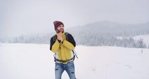 O homem do turista que anda através do campo que nevado obtém congelado, na parte superior da montanha, turista é equipado com to vídeos de arquivo