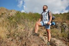 O homem do viajante com trouxa aumentou montanhas ajardina no fundo Conceito do estilo de vida ativo Imagem de Stock Royalty Free