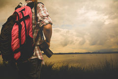 O homem do viajante com trouxa vermelha e a câmara digital ajardinam Imagem de Stock Royalty Free