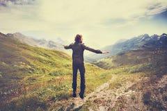 O homem do viajante que salta com montanhas ajardina no fundo Fotografia de Stock Royalty Free