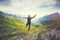 O homem do viajante que salta com montanhas ajardina no fundo Imagens de Stock