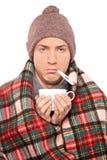 O homem doente cobriu com o cobertor que prende um copo de chá Foto de Stock Royalty Free