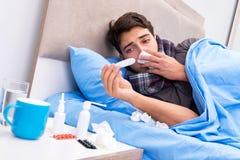 O homem doente com a gripe que encontra-se na cama Fotografia de Stock