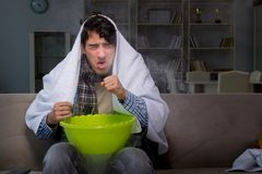 O homem doente que faz a inalação na noite na casa Fotografia de Stock