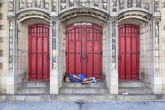O homem dorme na frente da porta da igreja na 7a avenida em New York City Fotos de Stock Royalty Free