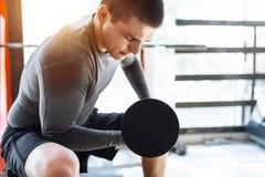 O homem dos esportes levanta pesos no treinamento no gym, treinamento da manhã imagem de stock