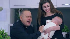 O homem e as crianças maduras, o vovô e a filha jogam com o bebê pequeno na cozinha em casa filme