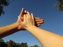 O homem e as mãos fêmeas tocam por suas palmas, isoladas contra o céu A mão da mulher está encontrando-se sobre a palma de um hom fotografia de stock