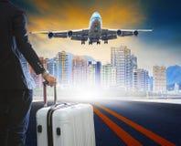 O homem e a bagagem de negócio que estão em pistas de decolagem do aeroporto com passen imagens de stock royalty free