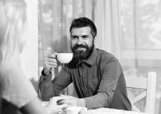O homem e a cara feliz guardam copo da bebida quente no fundo claro do café, defocused O indivíduo bebe o café ou o chá na tabela Fotos de Stock Royalty Free
