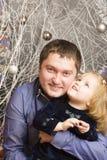 O homem e a criança estão entre decorações festivas Fotos de Stock