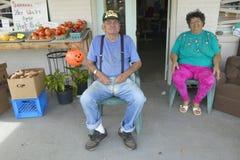 O homem e a esposa sentam-se na frente da loja pequena Fotografia de Stock