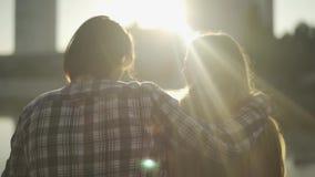 O homem e a fêmea sentam-se no banco e no olhar de rio na cidade vídeos de arquivo