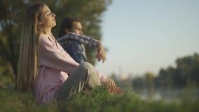O homem e fêmeas estão sentando-se no banco de rio filme