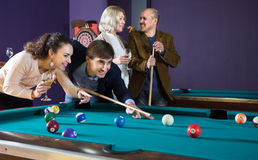 O homem e a jovem mulher batem uma bola nos bilhar, e olham cada um Imagens de Stock