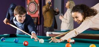 O homem e a jovem mulher positivos bateram uma bola nos bilhar foto de stock royalty free