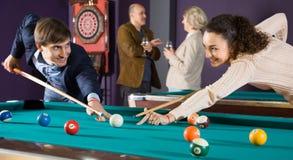 O homem e a jovem mulher positivos bateram uma bola nos bilhar Imagem de Stock