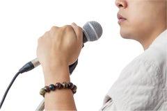 O homem e a mão que guardam o suporte do microfone cantam a música no whit Fotos de Stock