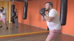 O homem e a menina farpados encaixotaram luvas no boxe de treino do gym, enganando ao redor, movimento lento, campeonato filme
