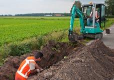 O homem e a mini máquina escavadora escavam uma trincheira para colocar cabos Fotos de Stock Royalty Free