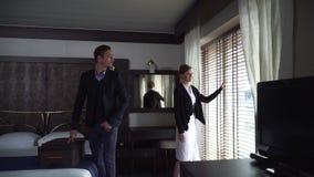 O homem e a mulher adultos chegaram no hotel moderno A menina vem à janela e olha nela, homem junta-se lhe filme